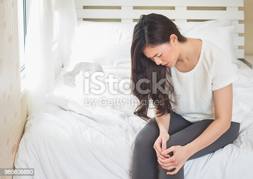 istock Asian woman holding knee in bed room, woman hurt pain at knee concept 985606680