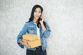 Asian woman holding pile of cardboard box or parcels using mobile phone