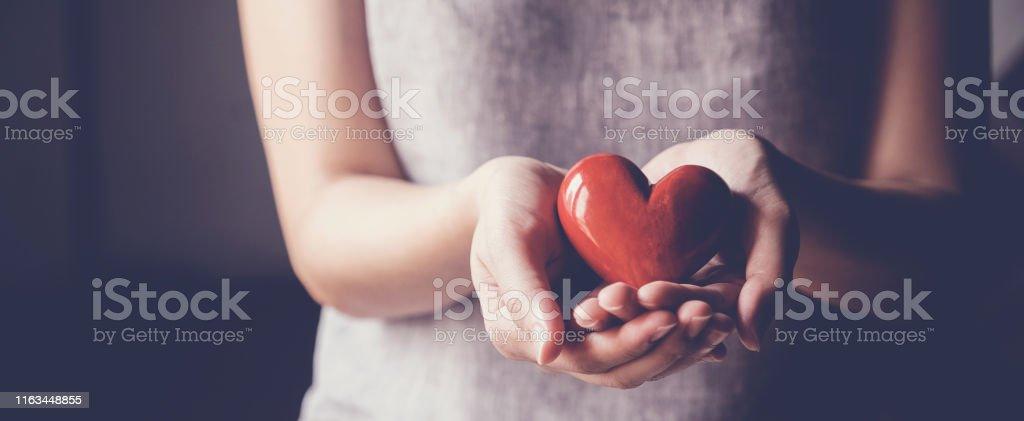 Asiatisk kvinna som innehar rött hjärta, sjukförsäkring, donation välgörenhet koncept - Royaltyfri Adoption Bildbanksbilder