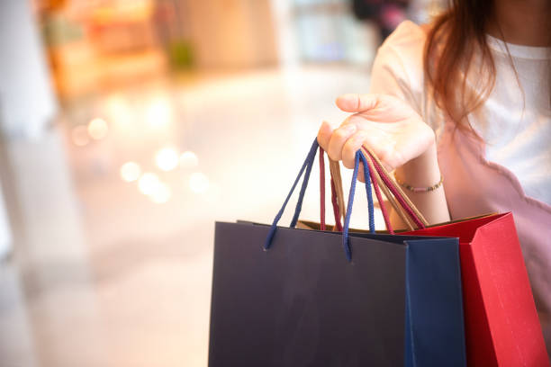Asian Woman Holding Shopping Bags In Shopping Mall Asian Woman Holding Shopping Bags In Shopping Mall consumerism stock pictures, royalty-free photos & images