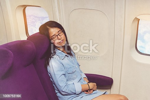 istock Asian woman in airplane 1009753164
