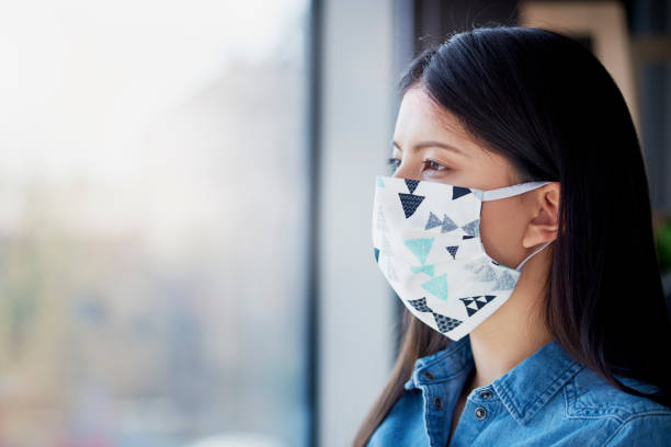 Asian woman in face mask looking through the window stock photo