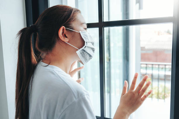 Asian woman in isolation at home for virus outbreak Coronavirus wearing a face mask quarantine herself stock photo