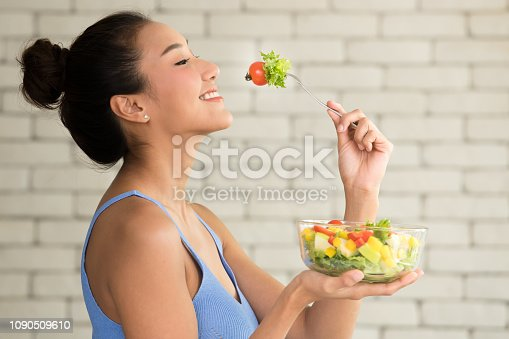 istock Asian woman in joyful postures with salad bowl on the side 1090509610