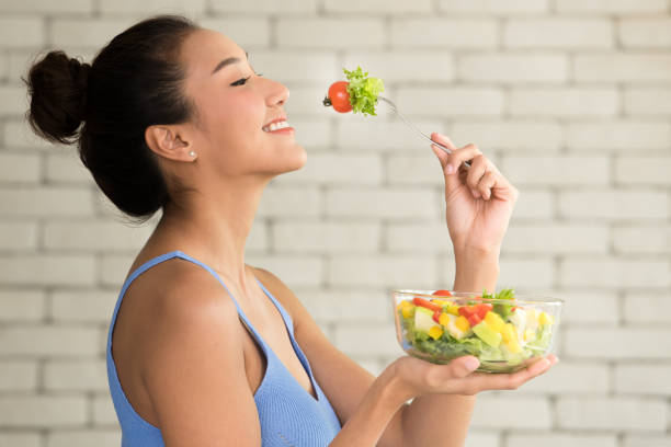 asian woman in joyful postures with salad bowl on the side - eating imagens e fotografias de stock