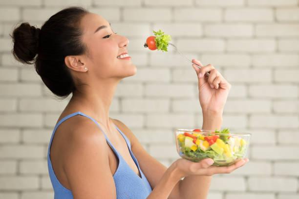 mulher asiática em posturas alegres com saladeira no lado - comendo - fotografias e filmes do acervo