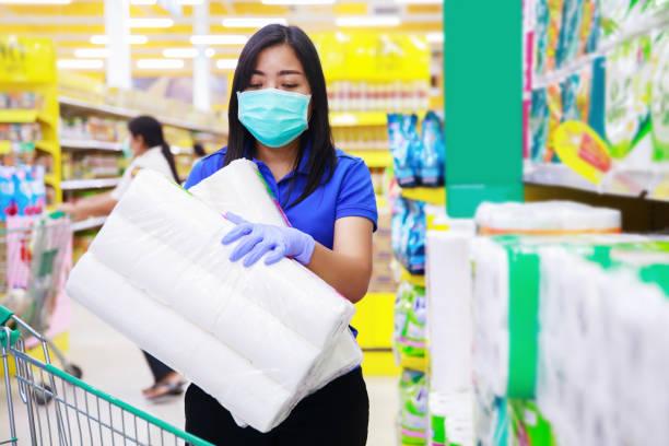 mujer asiática con máscara médica y guantes médicos elegir papel higiénico en el supermercado - foto de stock