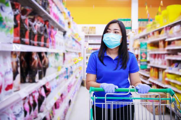 mujer asiática con máscara facial médica y guantes médicos de compras en supermarket.covid-19 propagando brote - foto de stock