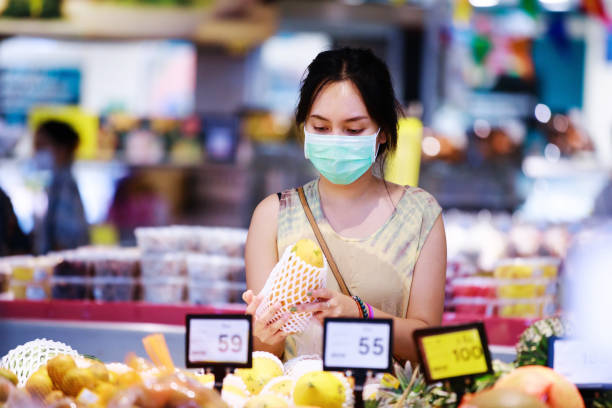 asian woman in medical face mask chooses fruits while shopping in supermarket