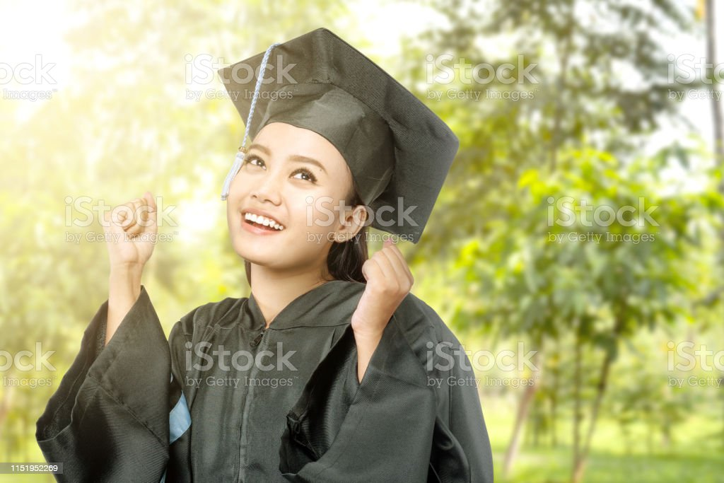 Asian woman in mortarboard hat graduating from college. Graduation...