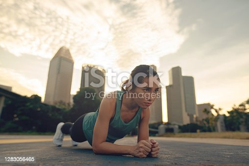 Asian woman in plank position against a city skyline