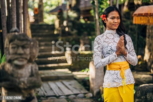 One woman, young lady in traditional Balinese clothing standing outdoors. with hands clasped.