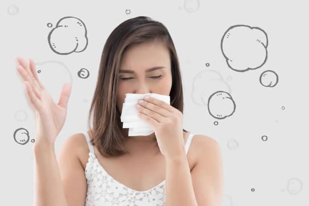 mujer asiática en vestido blanco captura su nariz debido a mal olor contra el fondo gris. - gangrena fotografías e imágenes de stock