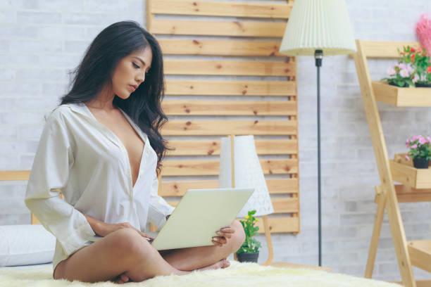 asiatische frau in weißem hemd mit laptop im schlafzimmer - damen shirts online stock-fotos und bilder