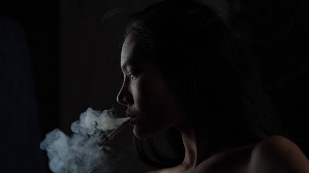 Asian woman inhaling and cigarette vaping. Female secretly smoking in bathroom at home. Concept of quit smoking and anti cigarette. stock photo