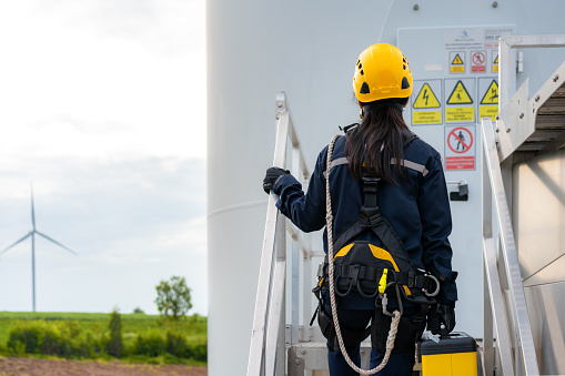 Asian woman Inspection engineer preparing and progress check of a wind turbine with safety in wind farm in Thailand.
