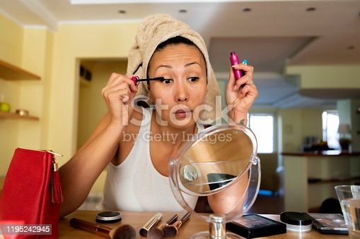 A beautiful woman of Asian ethnicity with a towel on her head is doing morning routine in a domestic bathroom while working on her eyelashes. A beautiful woman of Chinese ethnicity is standing in front of the mirror and doing make-up with a mascara.