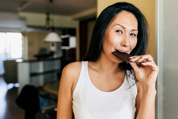 asian woman is enjoying in chocolate at home - cioccolata foto e immagini stock