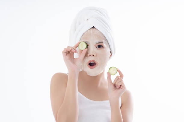 Asian woman is facial mask sheet .She is happy and surprise. stock photo