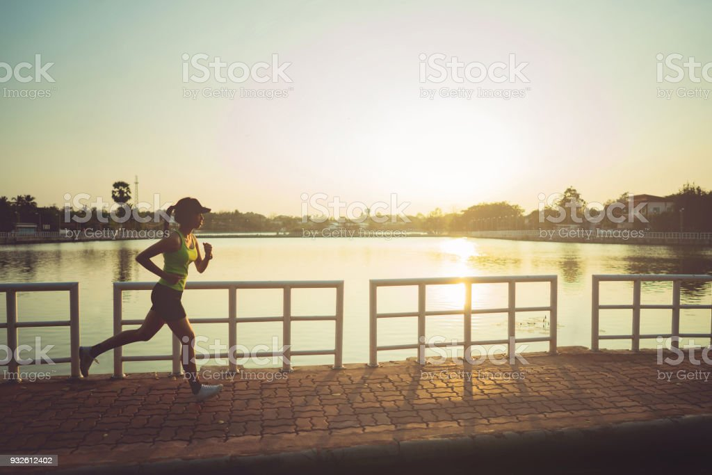 Asian woman jogging at the park. during the morning stock photo