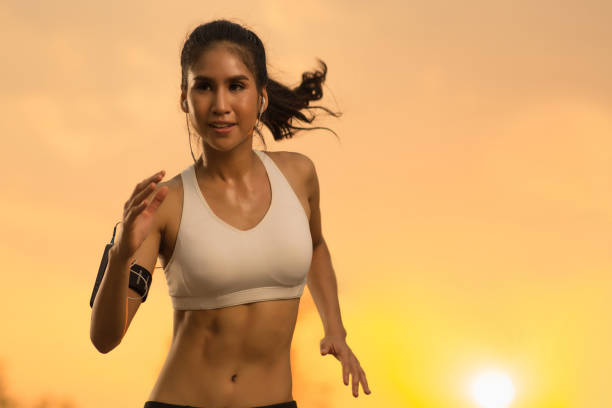 asian woman jogging in the evening - carpet runner stock photos and pictures