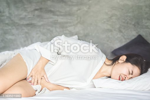 istock Asian woman laying down on bed suffering from stomach pain or period 1163531000