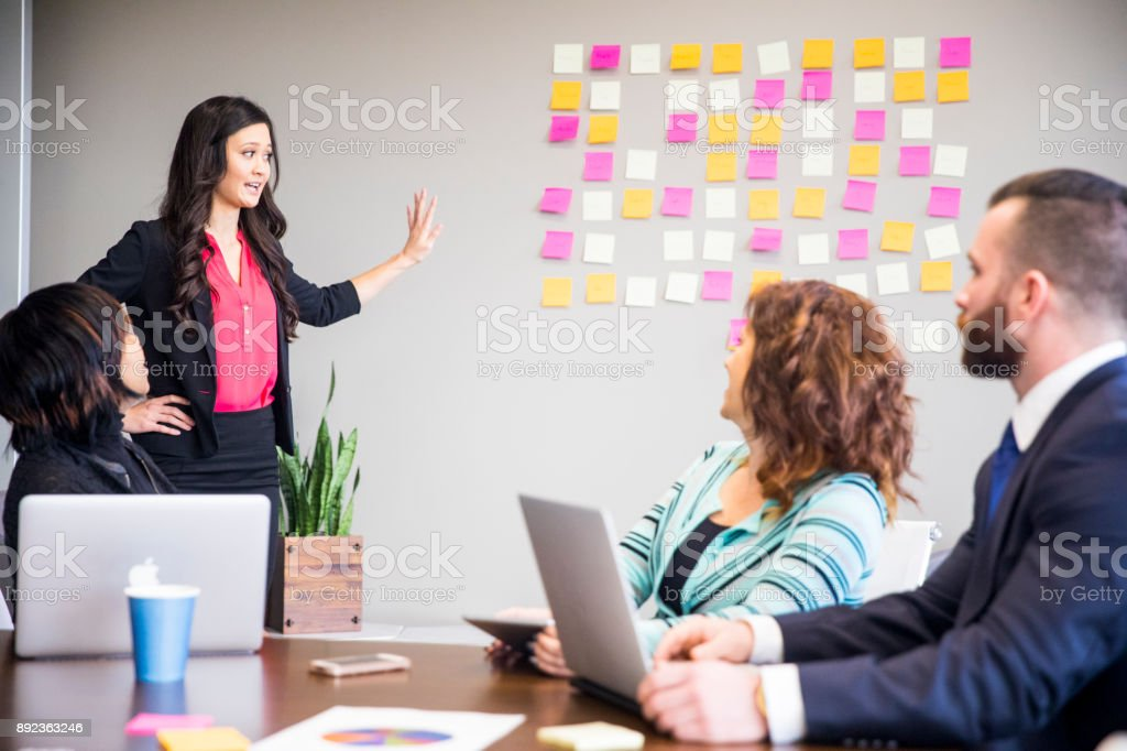 Asian Woman Leads Business Team Meeting in the Conference Room stock photo