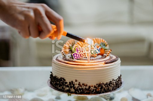 Asian woman lighting up candle on birthday cake