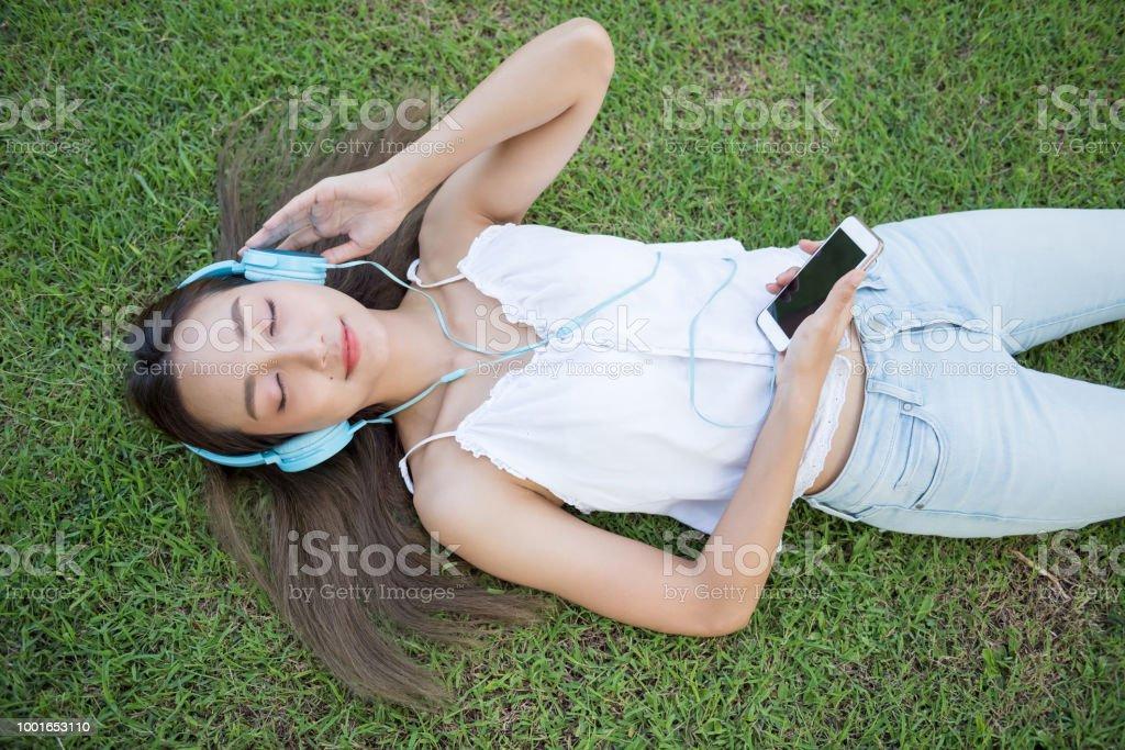 Asiatische Frau hören Musik auf Rasen – Foto