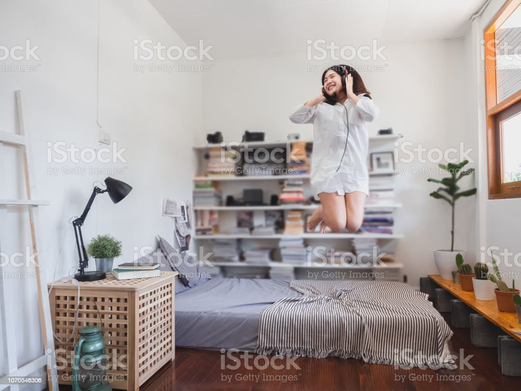 asian woman listening music and jumping on bed stock photo