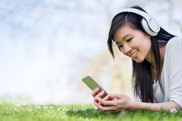 mujer asiática escuchando música al aire libre - mp4 fotografías e imágenes de stock
