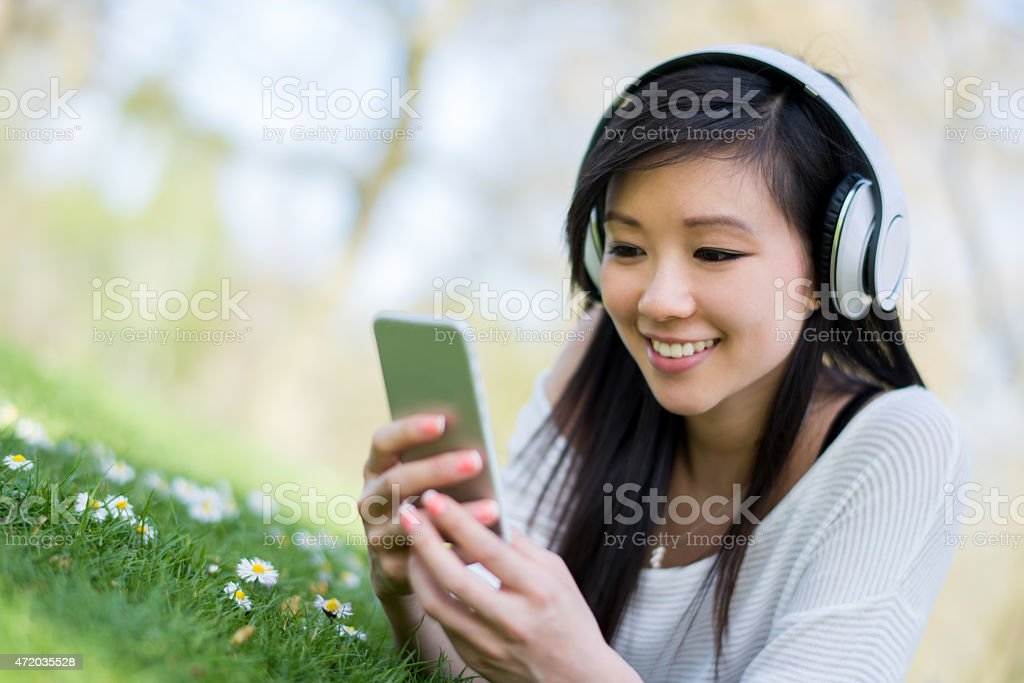 Asian woman listening to music stock photo