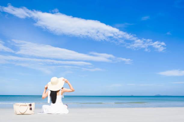 asyalı kadın, uzun siyah saçlı, beyaz elbise ve şapka dokuma çanta ve güneş gözlüğü yakınında plajda oturan giydi ve kopya alanı mavi gökyüzü ile deniz kenarında geri bakan, yaz tatili ve tatil konsepti - beyaz elbise stok fotoğraflar ve resimler