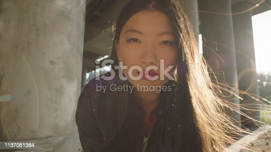 Young woman standing next to pillar. Portrait