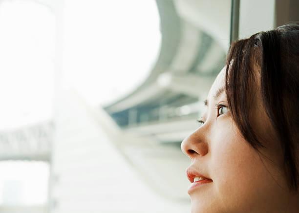 アジアの女性、お探しでモダンな構造の窓 - 女性 横顔 日本人 ストックフォトと画像