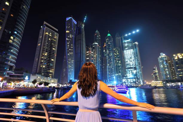asiatische frau, die das stadtbild von dubai - dubai urlaub stock-fotos und bilder