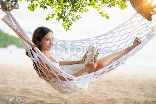 817409212 istock photo Asian Woman lying in a hammock on the beach and enjoying a book reading 1224971017