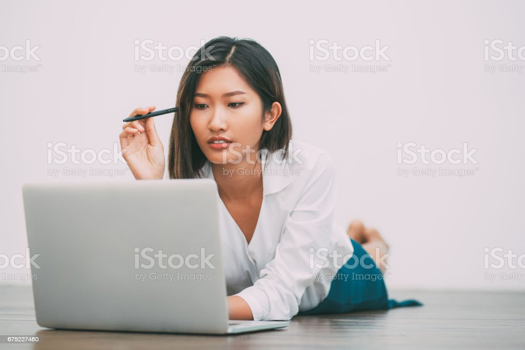 Asian Woman Lying on Floor and Working on Laptop royalty-free stock photo