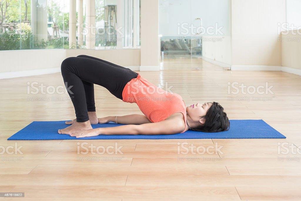 Asian woman make yoga Bridge pose in classroom stock photo