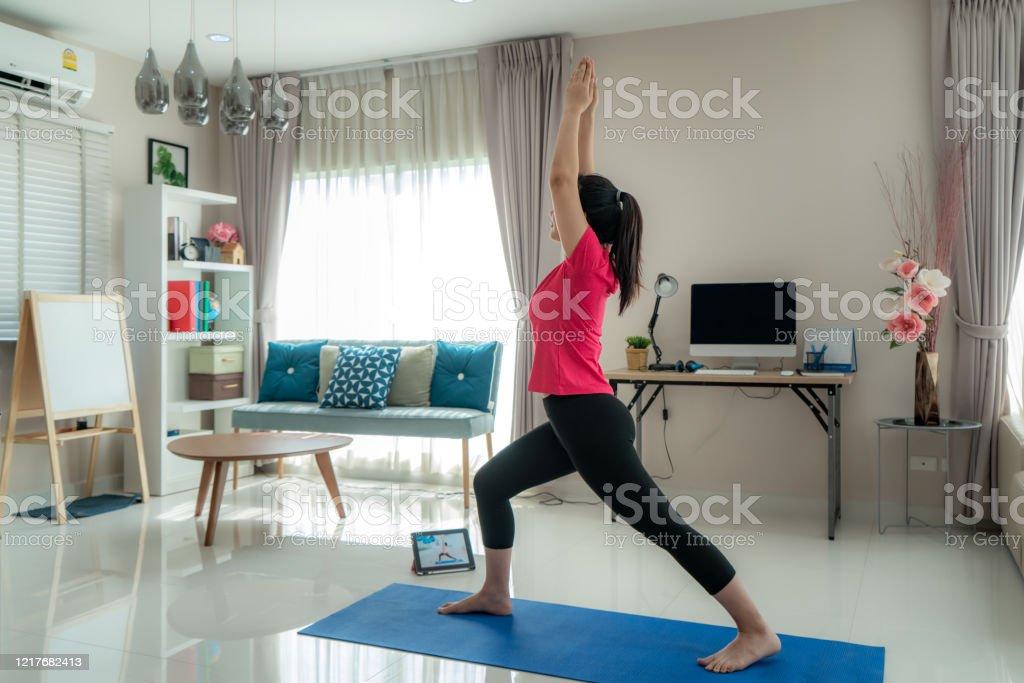 Mujer asiática haciendo ejercicio de yoga para alejarse de sus computadoras para tomar descansos de ejercicio al mediodía a través de clases de videos en vivo en tabletas digitales durante el trabajo desde casa. - Foto de stock de 20 a 29 años libre de derechos
