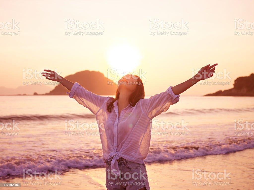 asian woman on beach enjoying sunrise stock photo