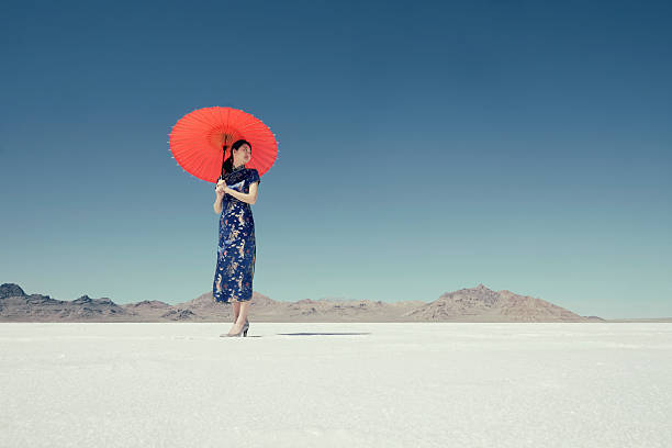 Asian Woman on Salt Flats A Japanese woman wearing a Chinese style dress, stands on the Bonneville Salt Flats holding a red umbrella. Taken during the daytime with a cloudless blue sky. bonneville salt flats stock pictures, royalty-free photos & images