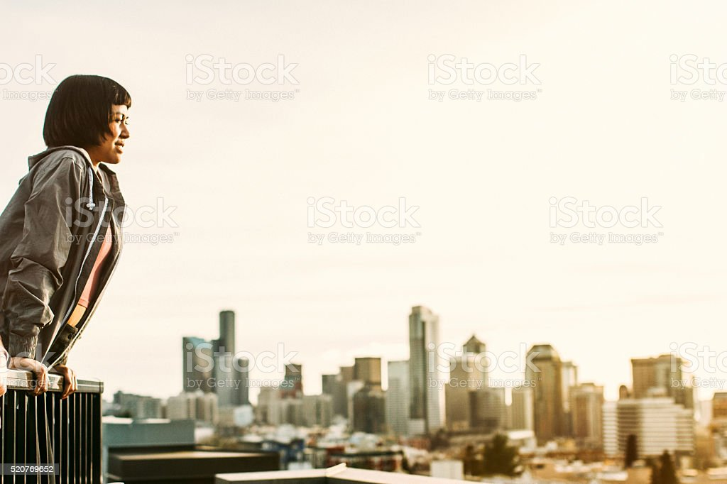 Asian Woman On Seattle Rooftop with Skyline stock photo