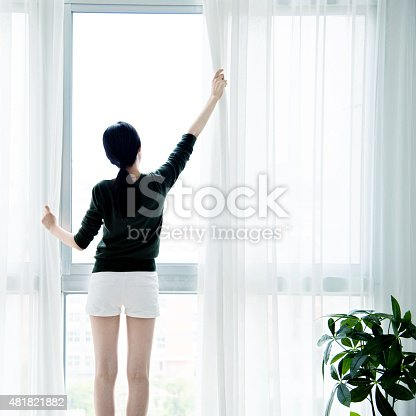 istock Asian woman open curtains 481821882
