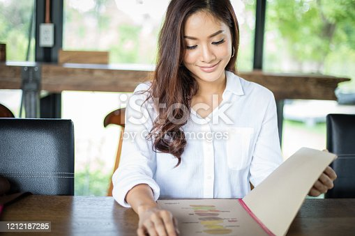Asian woman open menu for ordering in coffee cafe and restaurant and smiling for happy time