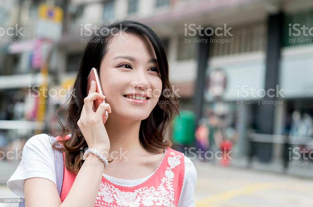 Asian woman outdoors on the phone royalty-free stock photo