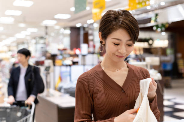 スーパーマーケットで再利用可能な綿袋でオレンジを梱包するアジアの女性 - sustainability ストックフォトと画像