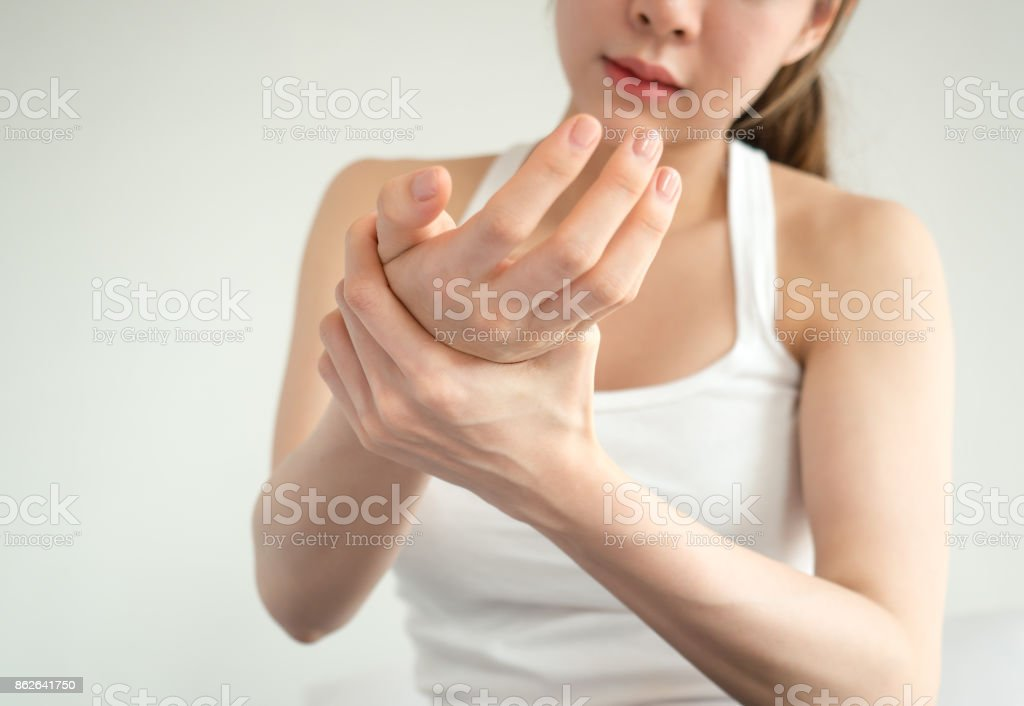 Asian woman pain at wrist, arm and hand, feel ache, Inflammation, woman muscle pain concept stock photo