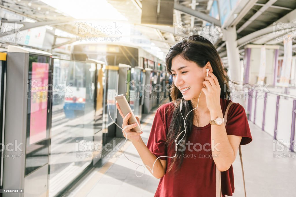 Asian woman passenger with casual suit using and listening the song via smart mobile phone in the BTS Skytrain rails or MRT subway for travel in the big city, lifestyle and transportation concept stock photo
