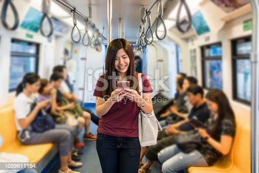Asian woman passenger with casual suit using the smart mobile phone in the Skytrain rails or subway for travel in the big city, lifestyle and transportation concept
